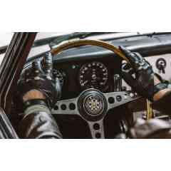 Type E - Gants de conduite en agneau nappa, patiné en pièce, perforations sur le dos de la main, couture interne des fourchettes,  bride de fermeture et bouton pression en nickel gravé d'un phœnix, logo de la maison. Fabriqué à la main. Ce gant reprend le motif de perforation du volant de la célébrissime Jaguar Type E.